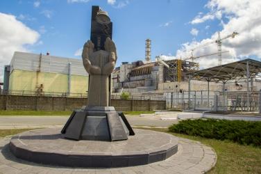 Het monument ter nagedachtenis van de slachtoffers van de ramp met de ontplofte reactor vier op de achtergrond.