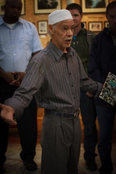 Gids Noor Ebrahim tijdens een van zijn rondleidingen. Als medeoprichter van het District Six Museum vertelt hij nog dagelijks het verhaal van de multiculturele wijk van weleer. Bron: Portland Seminary (Flickr, cc).