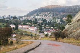 Bulembu met op de voorgrond de gerenoveerde rood-witte gebouwen en op de achtergrond de woningen waar de weeskinderen worden opgevangen. Bron: Kevin van Huët.